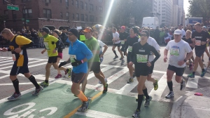 Runners in the 2013 New York Marathon turn on 1st Avenue on Manhattan, while thousands of people are cheering them. (Picture by Koen Blanquart)